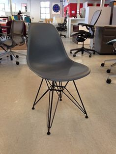 An Eames molded plastic chair in charcoal grey, by Herman Miller