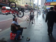Street Performer Balances Bike on Head While Playing Guitar