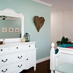 White turquoise walls add a fresh color to the feminine feel of this lovely bedroom. A white dresser with vanity mirror features a decorative top and bottom for a smooth finish. The white and turquoise are echoed in the peak at the bed frame and end bench. A wood heart adds warmth and decoration.