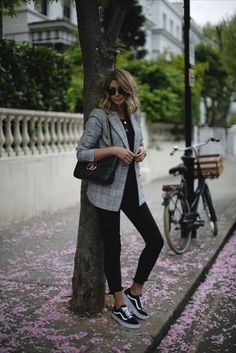 Full black outfit with a checked blazer and black sneakers. Relaxed and chic work outfit