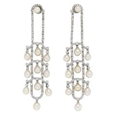A pair of Edwardian pearl and diamond chandelier earrings, with delicate diamond set open work frame suspending ten drop shape natural pearls all from a double diamond-set run beneath a pearl stud, all set in white with peg and scroll fitting, circa 1910
