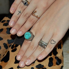 Finger tattoos. I like the cross but i would face it the other way