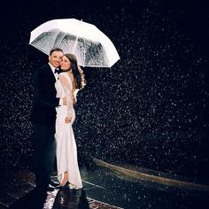"""Why We Love It: Don't let a little rain put a damper on your wedding day! We love this gorgeous photo.Why You Love It:""""I like this one; romantic with great lighting."""" —Betty J.""""Very beautiful!"""" —Tanya G.""""The light is amazing here.""""—Kinga P.Photo Credit: Sarah Tew Photography"""