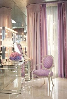 Beauty is personified in this purple dressing room where a mirrored wall and long violet drapes combine against a beautifully lit mirror. Everything in this purple hollywood regency dressing room is simply to fall in love with.