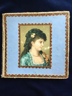 Old Vault Finds.... presents a late 1800s beautiful Victorian Woman on the front of a cardboard box that sold 6 Handkerchiefs per box. In this Pictured they captured her in a beautiful blue dress, with lace around her neckline, Black lace covering her head, with pink roses, and pearls. The side paper has a 3 dimensional geographic design.. This box had a silk purple ribbon... as seen on box  The Handkerchiefs that came in this box were embroidered, and Hemstitched cambric linen. Cambric…