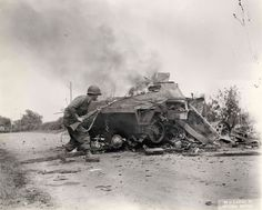 An American soldier cautiously approaches a just-destroyed German tank, in a U.S. Army Pictorial Service photograph. Note the grenade-launching adapter on his M1 Garand rifle.