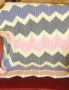 This eye-catching blanket is knitted in lovely squishy garter stitch. There are 2 sizes: the larger one, (shown here in rainbow colours) is suitable for a cot or throw, the smaller (shown in pink/mauve/grey) for a stroller but it can easily be made smaller or larger by adding/subtracting pattern repeats or rows.