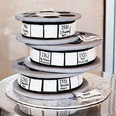 """Guinness-infused chocolate cake tiers—shaped and stacked to resemble film reels—bear the titles of the groom's favorite black-and-white movies."" by Rania's Catering"