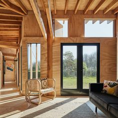 """The cabin has a cranked plan with the kitchen, dining and living space at the centre of the building, where the orientation shifts, and the bedrooms and bathrooms at either end. Softwood sheathing boards have been placed on all the walls and incorporated into the inbuilt furniture to create what the studio describes as a """"textured yet monotonous backdrop"""". Acoustic Baffles, Amsterdam, Vertical City, Timber Cabin, Timber Structure, Construction, Amazing Architecture, Cladding, Windows And Doors"""