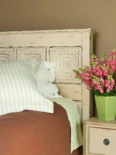 Tin Charm ~ This bedroom brings together the best of the old and the new. This standout headboard is fashioned from distressed white tin ceiling tiles. The antique look is contrasted by bright green and pinks that act as accent colors throughout the room, creating a charmingly eclectic look.