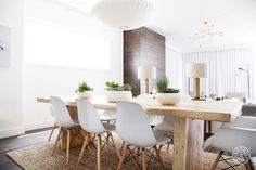 Modern dining room features a chunky wood slab dining table topped with bowls of cacti lined with white Eames Molded Plastic Chairs illuminated by a George Nelson Saucer Pendant atop a jute rug placed in front of sofa table topped with gold column table lamps, West Elm Pillar Table Lamps.