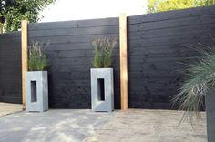 Nubuiten.nl Een mooie schutting, gemaakt van zwart Zweeds Rabat en zwarte Douglas potdeksel planken. De houten staanders tussen de schotten zijn van douglas hout.