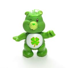 This vintage Care Bears toy is Good Luck Bear, he's green with a shamrock or four-leaf clover on his tummy. He has brown eyes and a tuft of green hair on top of his head. Good Luck Bear is poseable, h
