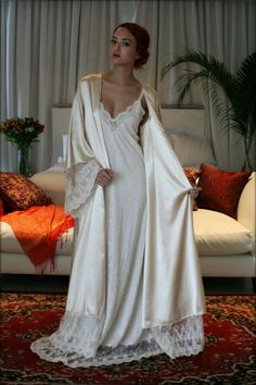 The Fiona robe is a decadent rich champagne satin accented with our beautiful embroidered Versailles French lace around the hem and wide angel sleeves. Shimmering satin glows on the outside and is just as delicious on the inside next to the skin for the utmost in luxury. A tie sash belt is included. The true beauty of this robe is the fabric. It is not your ordinary satin, it's a fluid blend with a bit of stretch that feels like watered silk. It is the most incredible fabric I've found...