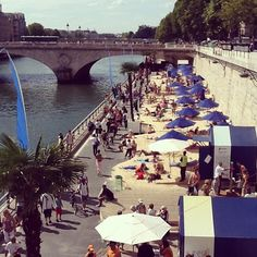 """Summer in the city.....the banks of Paris' Seine River adds an artificial """"Paris Beach"""" full of recycled sand, palm trees, beach umbrellas, and sprinklers."""