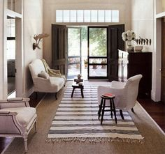 It's common to see striped cotton rugs set over sisal to introduce pattern, since the natural fiber helps keep the lighter weight textile in place. A black-and-white striped rug looks terrific in the great hall of this rural Alabama plantation house where designer Betsy Brown used this favorite high contrast combo to tweak up a super-neutral space.