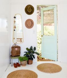 Down to earth: Embrace simplicity in a mudroom with clean white walls and natural touches like potted plants and seagrass rugs. A pastel-colored door contrasts the walls and tawny accents for a modern feel.