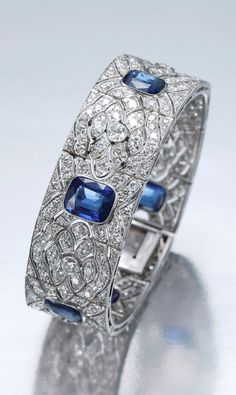 JANESICH - AN ART DECO SAPPHIRE AND DIAMOND BRACELET, CIRCA 1920. The articulated strap of geometric pattern pierced with stylised navette motifs, centring on six cushion-shaped sapphires within a ground of circular-cut diamonds, mounted in platinum, signed.