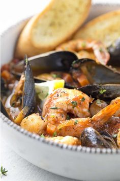 Bowl of seafood stew with slices of bread