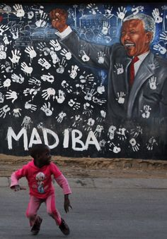 A young girl plays in front a mural depicting former South African President Nelson Mandela at the Alexandra township in Johannesburg, South Africa, Tuesday, July 17, 2012, to honor Mandela's 94th birthday