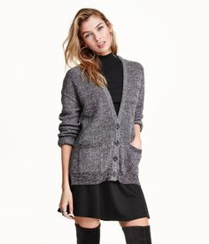 Fine-knit, V-neck cardigan in a cotton blend. Buttons at front, slits at sides, and patch pockets.