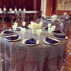 Event Design by RS Event Productions in Dallas. Patterned linen paired with ghost chairs. White Chargers, goblets and simple spider mum and orchid centerpieces.