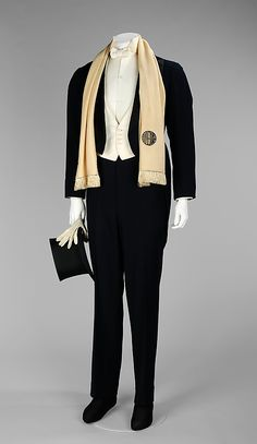 Men's evening suit (including scarf, gloves, and top hat) by Brooks Brothers, American, 1933. Brooks Brothers was a very prestigious men's tailor in the 1930s. This ensemble is complete down to the accessories and conveys the overall elegance of the formal look. Dress suits like this were known as white tie and were appropriate dress for the most formal evening events. Brooks Brothers was founded by Henry Sands Brooks in 1818 in New York City as a ready-made and custom men's clothier.