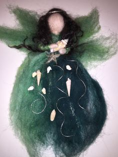 This delightful felted wool fairy wears a dress of ocean blues and greens. Like her mermaid friends, she treasures her bounty from the sea, a sea