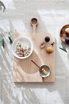 Morning granola bowl with yogurt and fruit on a wooden board