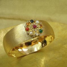 Navratna Kada - The symbolic arrangement of the nine astrologically important gemstones, the 'navratna', sits on a broad gold kada handcrafted in 22k yellow gold, rendering itself contempory in style.