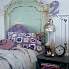 Beautiful turquoise bed that looks like it's made from architectural salvage / Pretty accessories: purple granny-square pillow, large alarm clock, metal bedside lamp , numeral 2