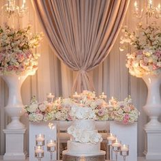 Kicking off with this couple's table that was engulfed in mounds of flowers and framed by two massive urns filled with blooms. The setup was made complete with four suspended crystal and a sof Head Table Wedding, Wedding Stage, Dream Wedding, Sweet Heart Table Wedding, Cake Table Decorations, Reception Decorations, Event Decor, Flower Centerpieces, Flower Arrangements