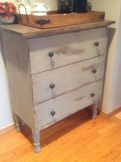 Description: Using an ikea Tarva dresser as a blank canvas. We first replaced the legs with curvy new legs from Home Depot. We painted and distressed the dresser with chalk paint. And then we placed new distressed stained wood boards in various widths next to one another as a new top.