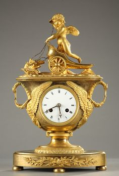 An exceptional gilt bronze mantel clock with its key depicting a winged putto in an antique chariot pulled by two doves resting on a platform adorned with water leaves.