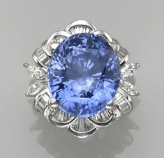 A sapphire, diamond and platinum ring  centering an oval-shaped sapphire, set vertically within a baguette-cut and pear-shaped diamond surround.  Sapphire weighs an estimated: 23.80 carats; estimated total diamond weight: 1.00 carat.