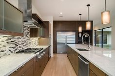 Gorgeous kitchen // Glass tile backlash, quartz countertops, rich cabinetry, stainless appliances and light hardwoods
