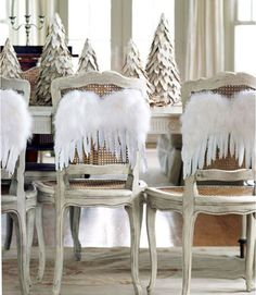 A row of birch-bark trees makes for a simple yet stunning centerpiece. Dining chairs get into the holiday spirit with angel wings.