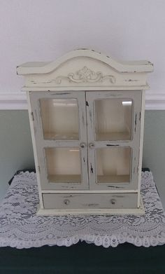 "Vintage Upcycled Jewelry box / Shadow box/ Curio box that has been hand painted in a cream colored white and a light olive green. This box has a highly distressed look and will be perfect for a chippy or shabby chic look. This Upcycled jewelry box/Shadow box has twin opening doors and a drawer on the bottom, has all original hardware. Box measures approximately 15 ½"" in height x 10 ¾"" in width. This piece was found at an Estate sale, it is very shabby chic, comes as is, is sturdy, and in…"