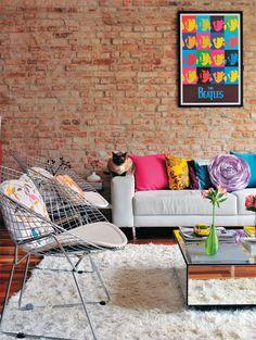 Acessórios para lá de coloridos trazem vida ao mobiliário neutro nesta sala de tijolos aparentes.
