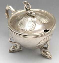 A Victorian silver mustard pot, the circular conical form raised on shell mounted stylised dolphin feet and conforming terminal to the hinged lid opening to the blue glass liner. Hallmarked Birmingham 1862,