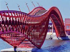 """Puente Pythonbrug  Con sus 93 metros, probablemente se trate de uno de los puentes más singulares de Amsterdam por su característico color rojizo en forma de serpiente, uniendo Sporenburg con la isla de Borneo. Diseñado por el estudio de arquitectura West 8 y ganador de la International Footbridge Award, el puente fue inaugurado en 2001, siendo conocido comúnmente como """"Anaconda"""" o """"Puente Pitón""""."""