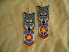 Wolves are the supreme hunters. They can help you find resources you need and guide you when you feel lonely or lost. -- A perfect gift for a wolf lover or one with a wolf spirit. -- Over 1,300 Delica beads were woven in the brick stitch method to give the piece excellent presentation and the feel of soft leather. -- Approximately 3.75 inches long with the ear wire. 1 inch wide. -- Gold plated ear wires include silicone backing to prevent earring loss. -- Can be changed to posts or clips at…