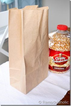 Air-pop your own popcorn in a paper bag. Instructions here, very easy - kernals+bag+microwave.