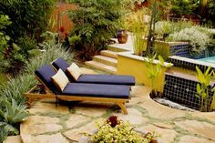 Hardscaping. The emphasis is on the usable living space; plants are used to enhance the patios and tends to be on the perimeter and in containers. This patio is made of peach-toned flagstone with the spaces filled with soft ground cover. The lounge chairs face a luxurious pool with a cobalt-blue tiled wall fountain.