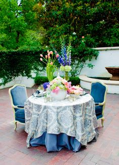 Decor Blue armchair velvet vintage white seating chair lounge Chic posh sweatheart head table layered linens damask overlay coral tulips gladiolus fountain patio greenery trees
