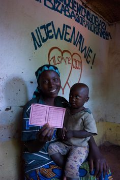 Jeannette Twishima smiles, holding her 22-month-old daughter, Charlène Bisengimana, as she displays the child's health card inside their home, in Nkoyoyo Colline in the north-eastern Muyinga Province of Burundi. They have just returned from the immunization outreach post at the market. The health card contains the record of the child's vaccination against measles during the UNICEF-supported immunization campaign.    © UNICEF/NYHQ2012-0482/Christine Nesbitt    http://www.unicef.org