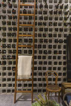 Projeto do escritório de arquitetura Triart para Casa Cor São Paulo 2016, que utilizou blocos de concreto para armazenar garrafas de vinho.