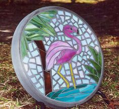 Stained glass and concrete stepping stone. Beautiful, bright stained glass depicting a Flamingo Oasis - The stone is custom made with the stained glass being hand cut and concrete hand poured forming a 14 round stone 2 in depth. Beautiful used as a stepping stone or propped up in garden or deck or porch for colorful decoration. These stones can also be used as tabletops to make great side or cocktail tables on the porch or anywhere in the home.