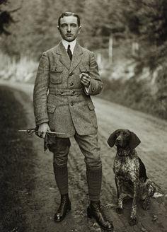 Nesta foto podemos ver um homem com cercas de 35. Encontrase bem vestido segurando um cigarro na mao esquerda e na direita parece uma trela e um pau. Parece uma pessoa da classe alta, ou professor ou empresário. Ao seu lado encontrasse um cão sonetado parecendo me a mim que este cão tem pedigree.