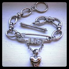 Juicy Couture safety pin charm bracelet This adorable post-and-loop style bracelet has amazing details all over it! There are crowns on the edges of the post, a juicy couture banner on the hanging heart, and to top it off, the main part of the chain is fashioned in a way that each link looks like a bow! Juicy Couture Jewelry Bracelets